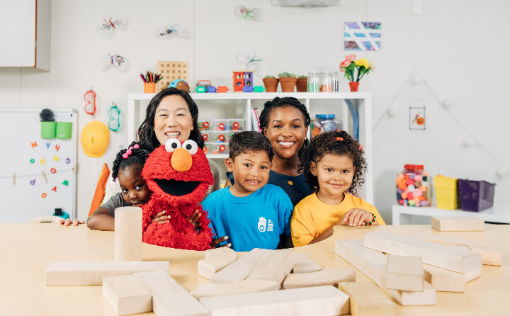 Priscilla Chan poses with Elmo, a teacher and school children
