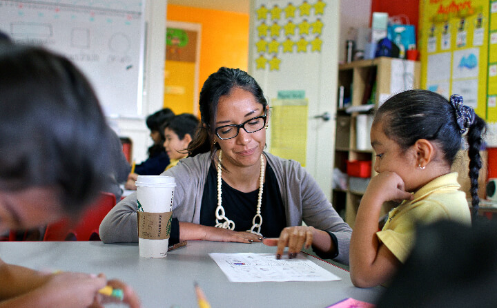 A Chan Zuckerberg Initiative employee works with a young student inside the classroom