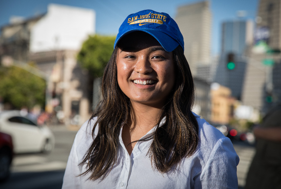A smiling female undocumented student with baseball cap standing on a street in a city.
