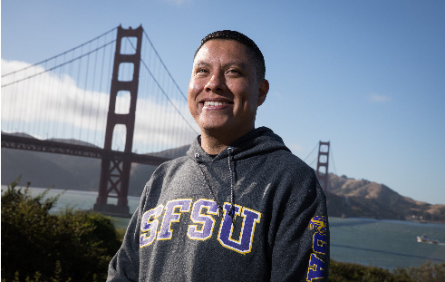 A smiling male undocumented student in front of golden gate bridge