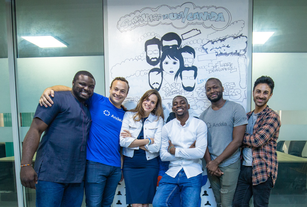 Group of men and one woman smiling (two of the men wearing a T-shirt from Andela)