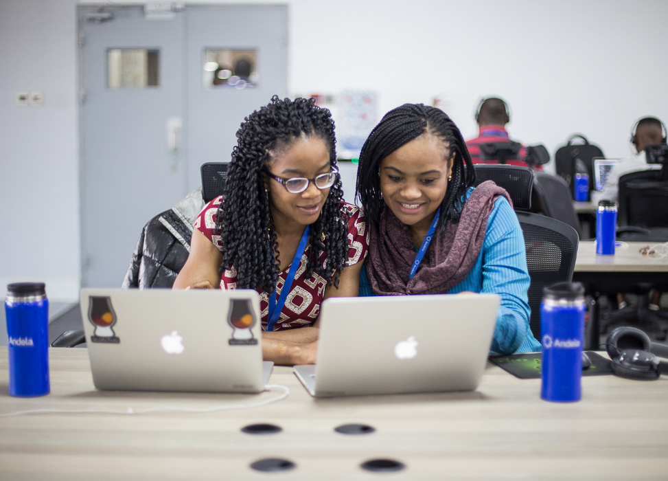 Two black female computer engineers sitting at a desk with laptops working together