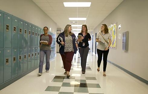 Four female educators walk down a school hallway with lockers.