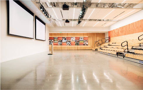 Large event space with bleachers on the right, retractable screens on the left, a podium and a photo mural on the back wall