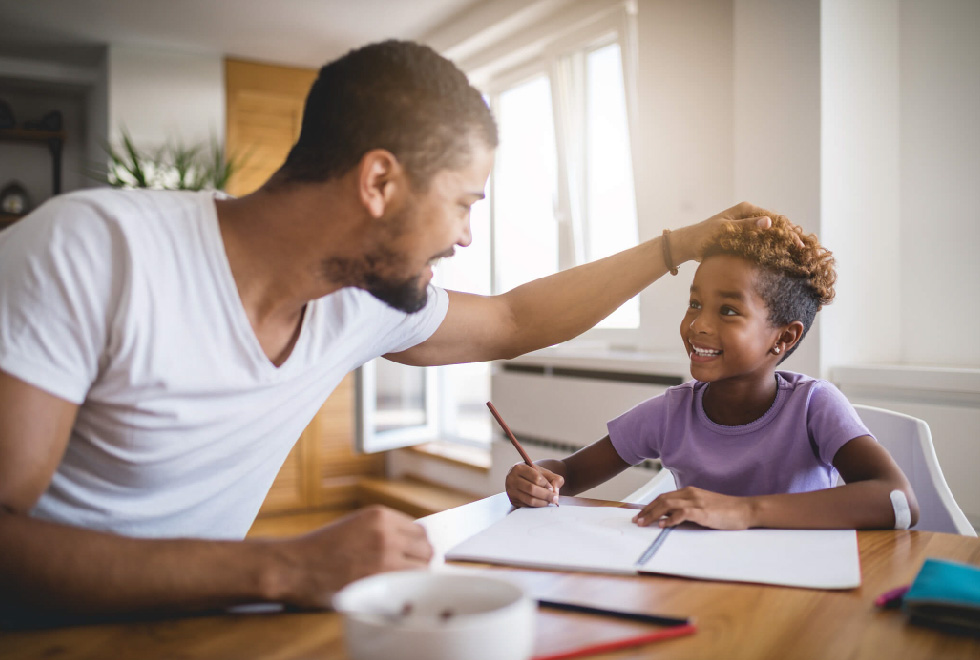 Smiling black father helping smiling daughter with school work