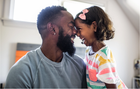 Black bearded father laughing with young daughter heads touching