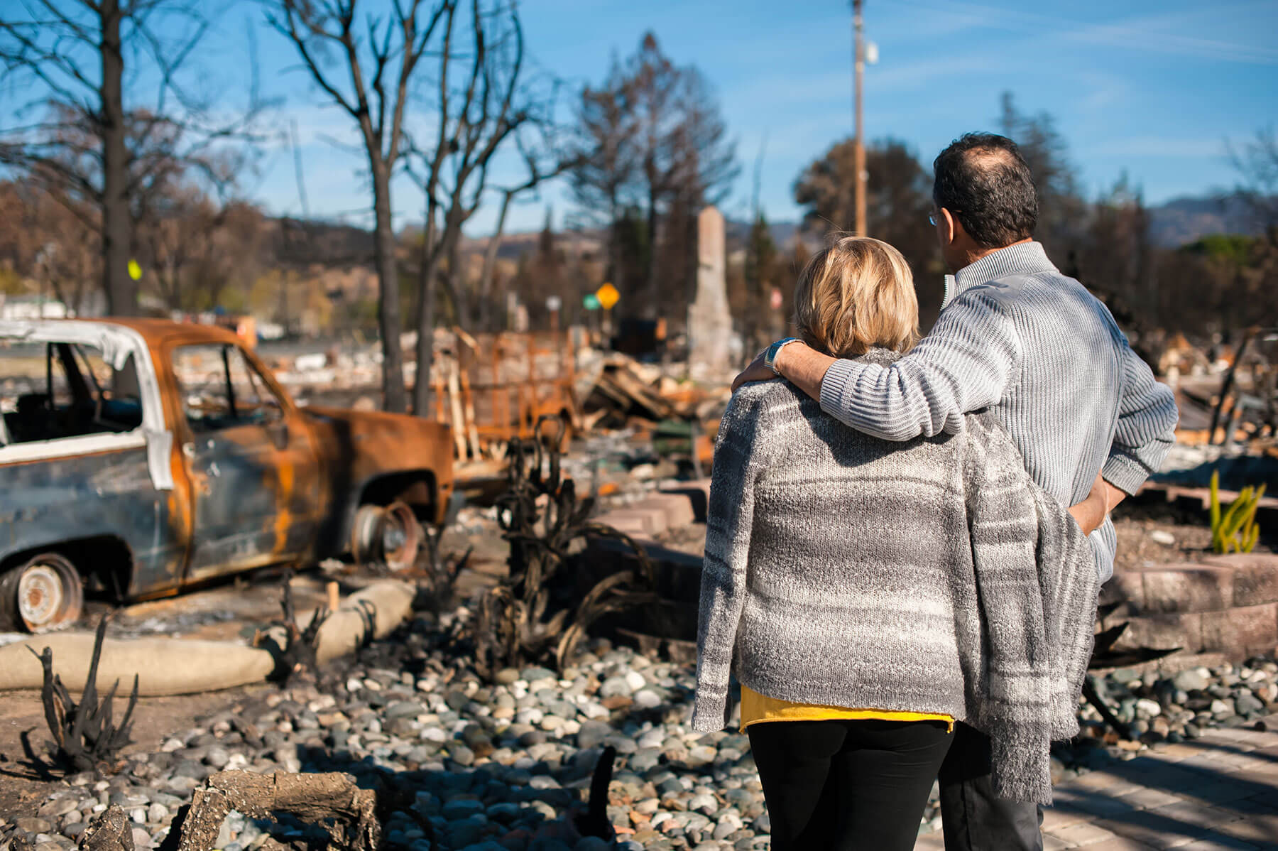 Couple standing facing in front of their fire-damaged home, charred car and trees in the background