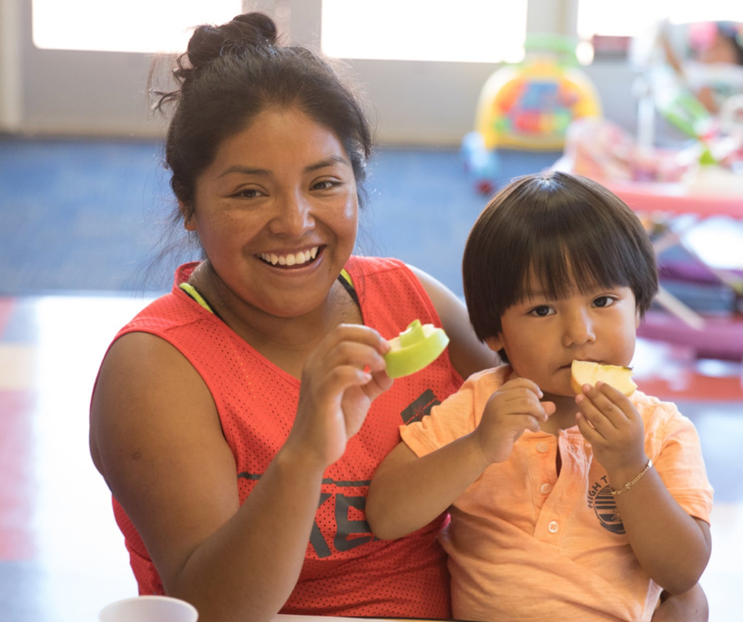 Silvia Isaac and Juaquin, eating snacks at the East Palo Alto YMCA's Nana Y Yo program to help caregivers and pre-school age children focus on developing and learn together.