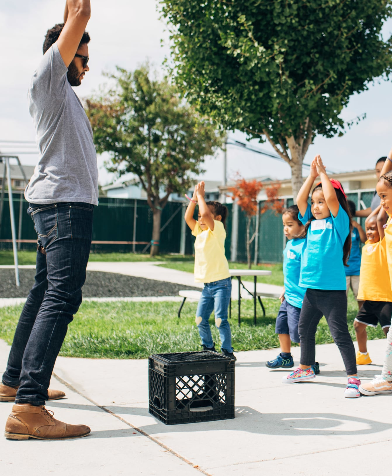 Mr. Vosa Cavu-Litman leading a class of Pre-Kindergarteners in an outdoor activity on the first day of school, at the Primary School in East Palo Alto