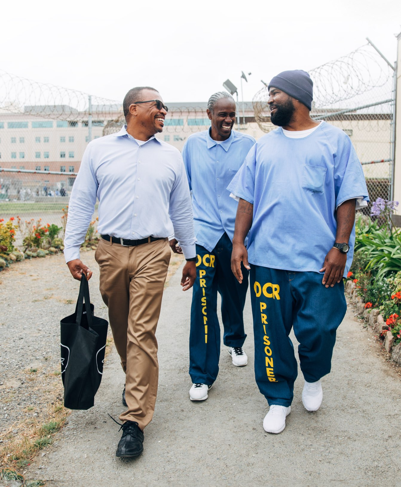 "Aly Tamboura, Justice & Opportunity at CZI, Richard ""Bonaru"" Richardson, and Earlonne Woods, co-Host of EarHustle, catch up during a recent visit at San Quentin."