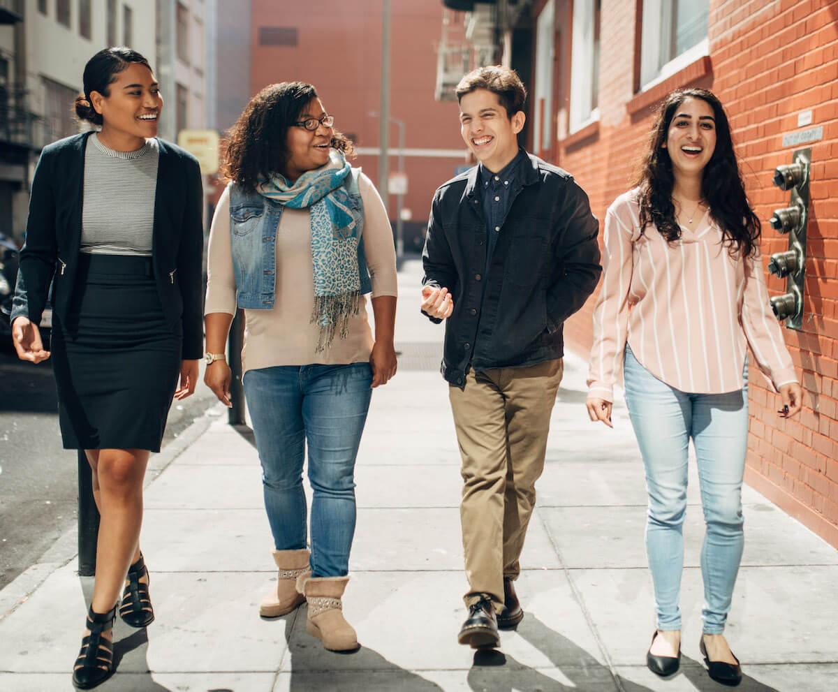 Four Non-Profit Housing Association (NPH) Bay Area Housing Inaugural Internship Program interns, walking together and smiling (CZI Housing Affordability).