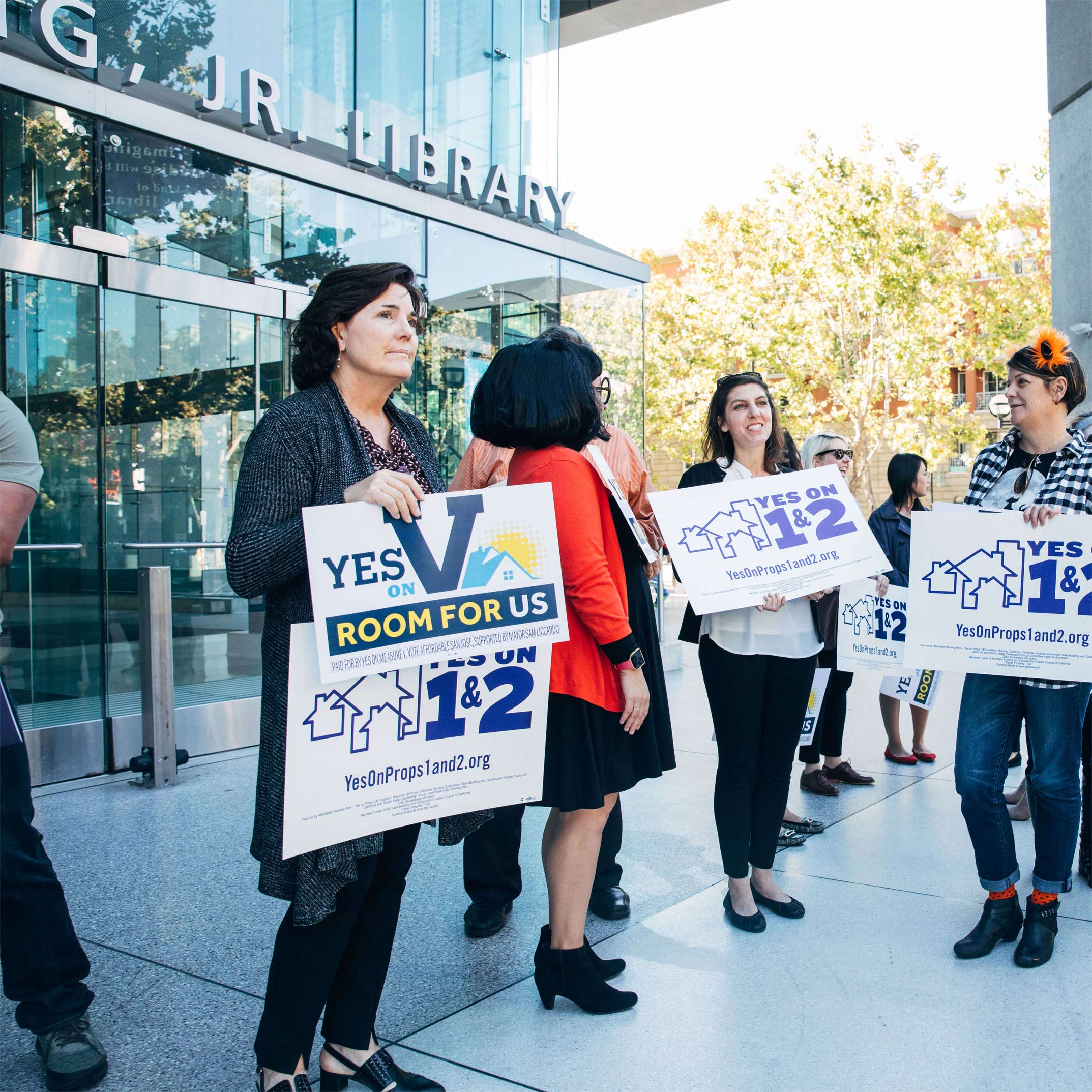 Advocates stand in front of the Library in San Jose in support of ballot initiatives Measure V, and Propositions 1& 2 that support affordable housing in Santa Clara County.