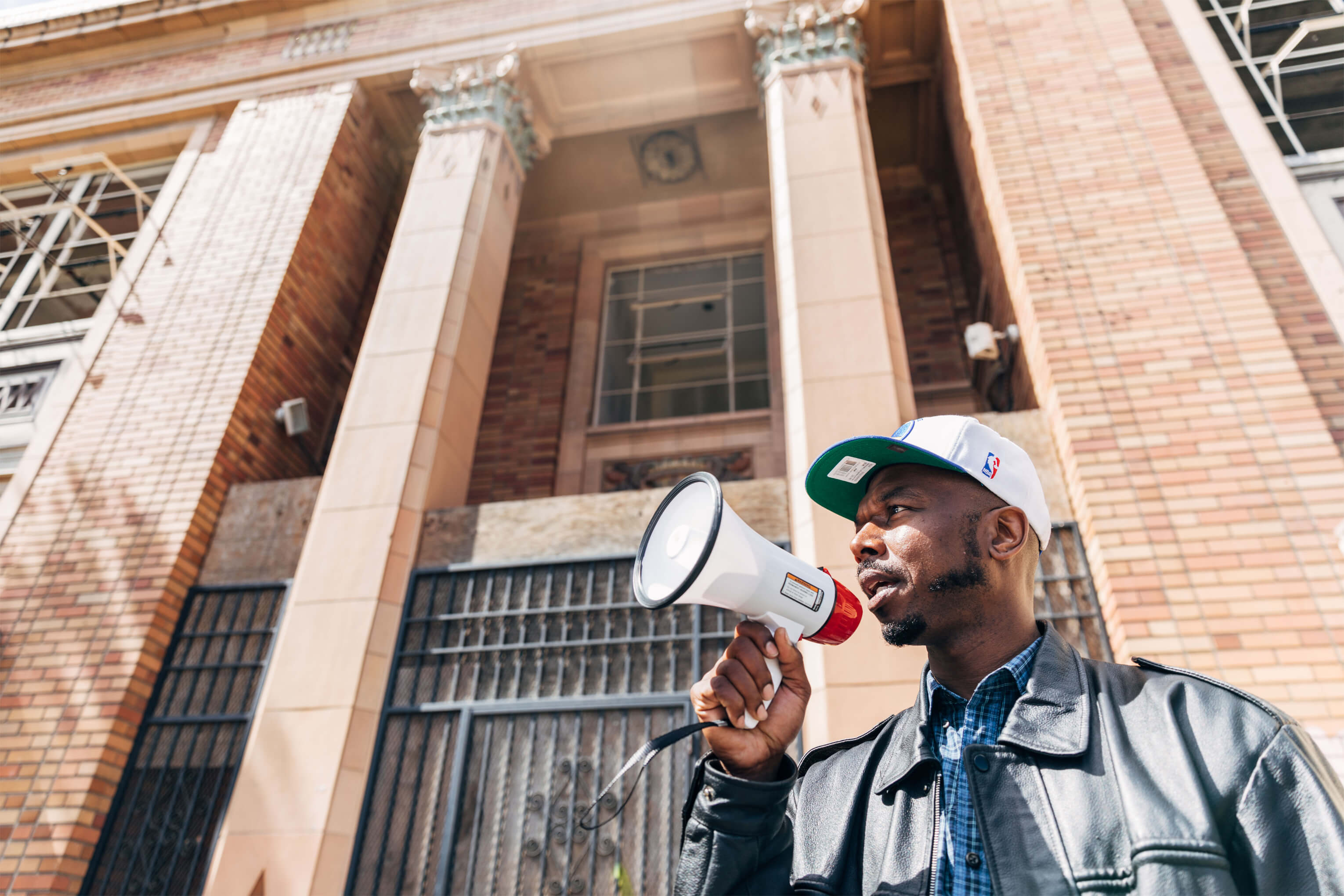 "John Jones III, a housing advocate and Bay Area native, recites an ""I believe"" chant outside of the former Safeway headquarters building where his grandparents used to work, in East Oakland, California."