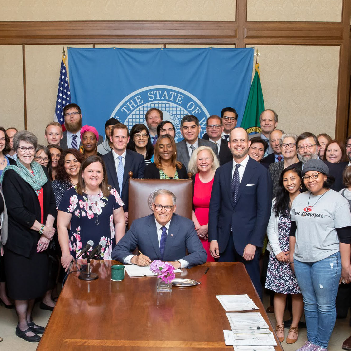 Tarra Simmons stands beside Washington Governor Jay Inslee, who is signing the New Hope Act bill
