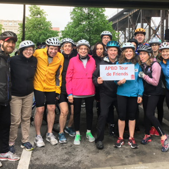 """Group of smiling APBD Research Foundation cyclists wearing bicycle helmets and holding a sign that says """"APBD Tour de Friends."""""""