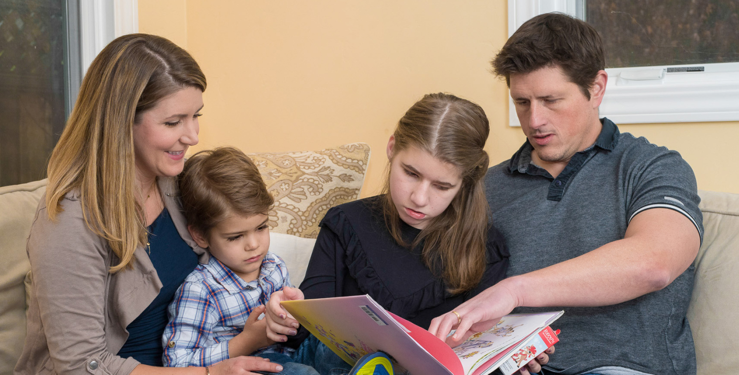 Kim Nye (far left), her husband Zach (far right), and their children Tessa (right) and Colton (left) read a book together on the couch