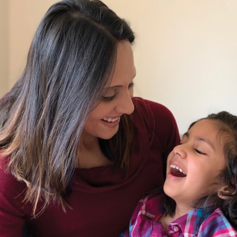 INADcure Foundation president and co-founder holding her young daughter, who has the rare disease Infantile Neuroaxonal Dystrophy, as both smile.