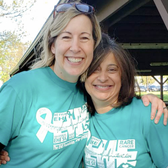 Two smiling women with arms around each other wearing blue t-shirts for The EHE Foundation (Epithelioid Hemangioendothelioma).