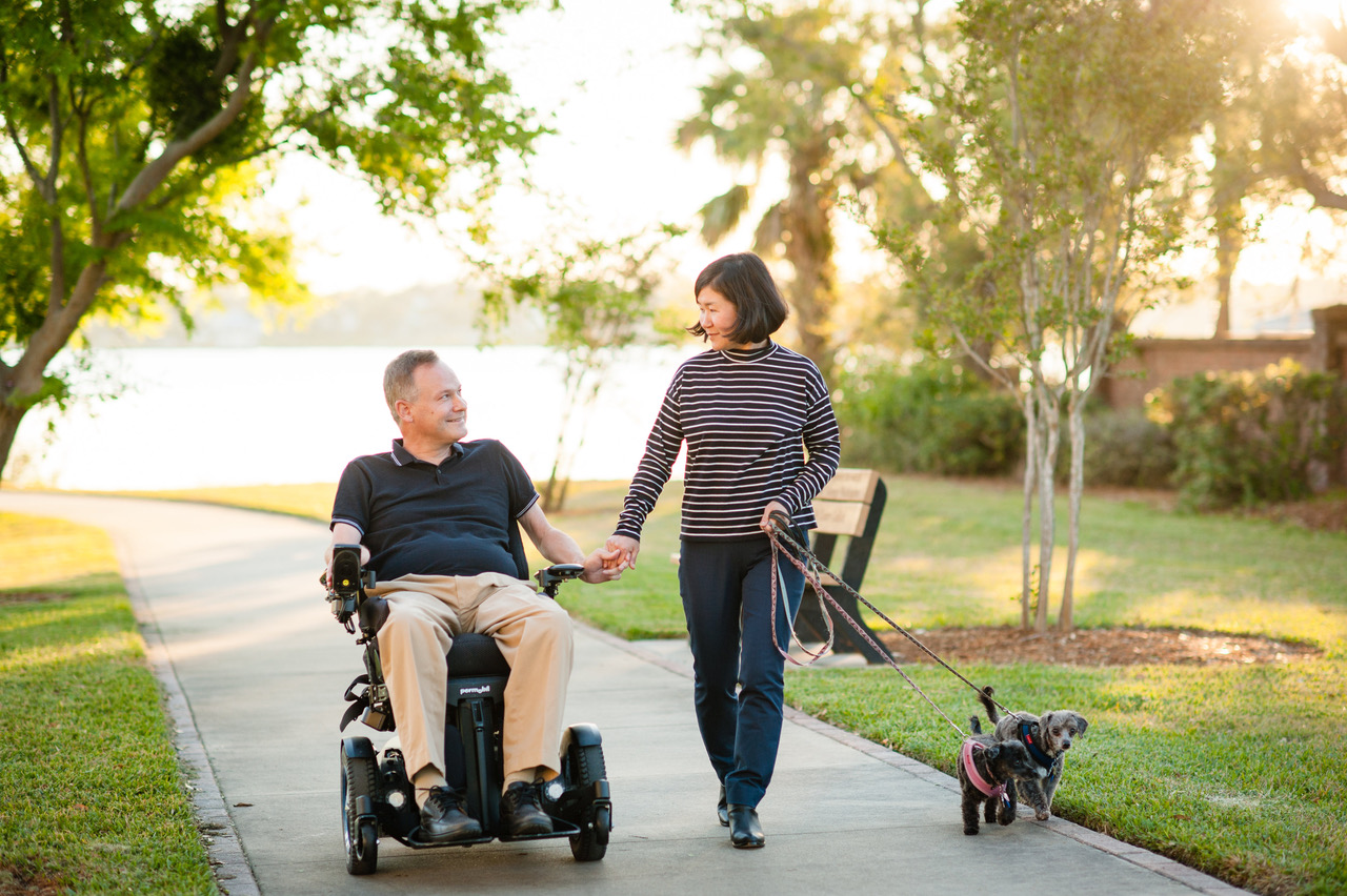 Josh (left) and Eunha (right) Thayer walking outside with their two dogs