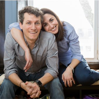 I AM ALS male and female couple smiling and posing together in front of a window.