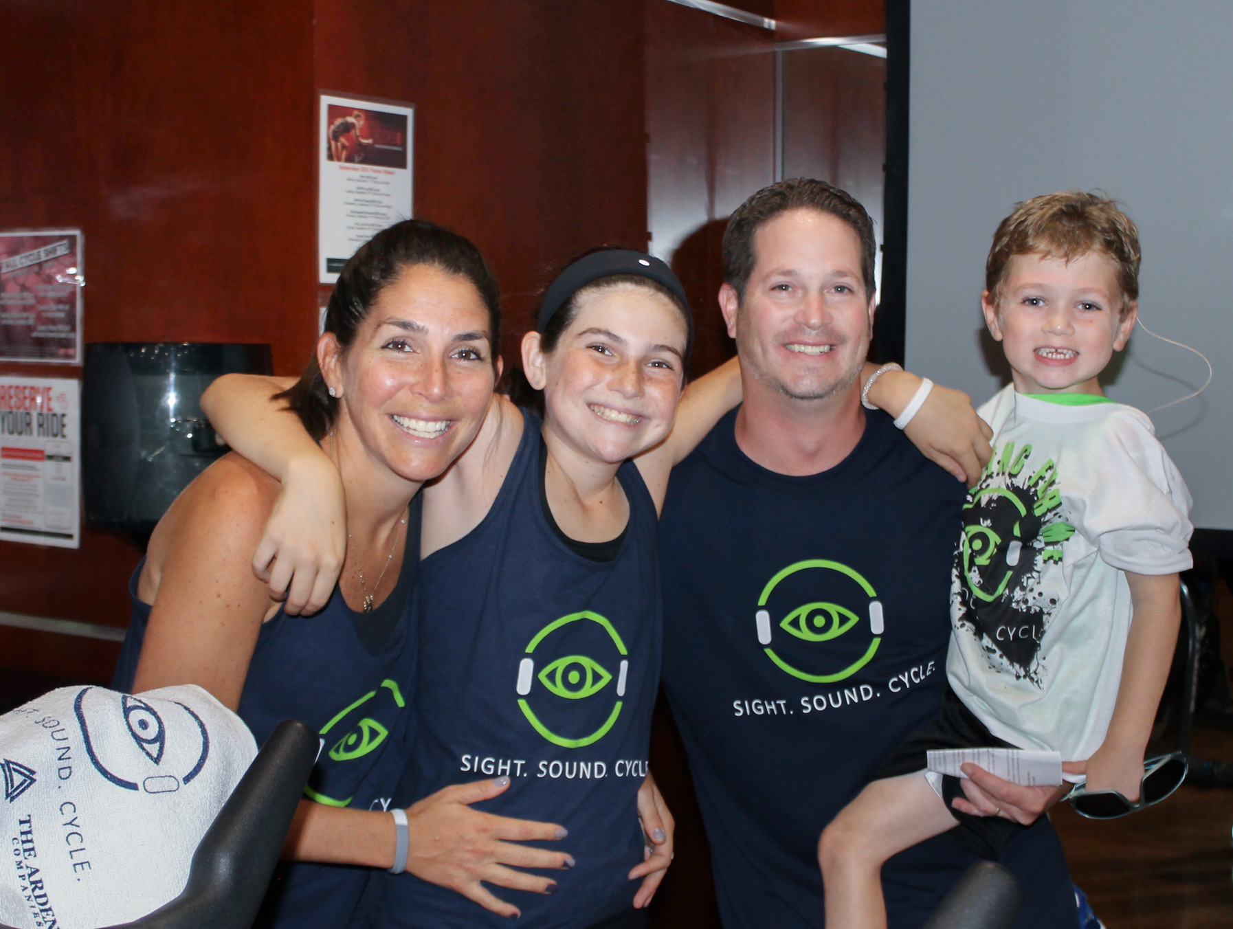 The Root family, Rachel (far left), Emily (left), Jared (right), and Zachary (far right), pose for a photo at a cycling event