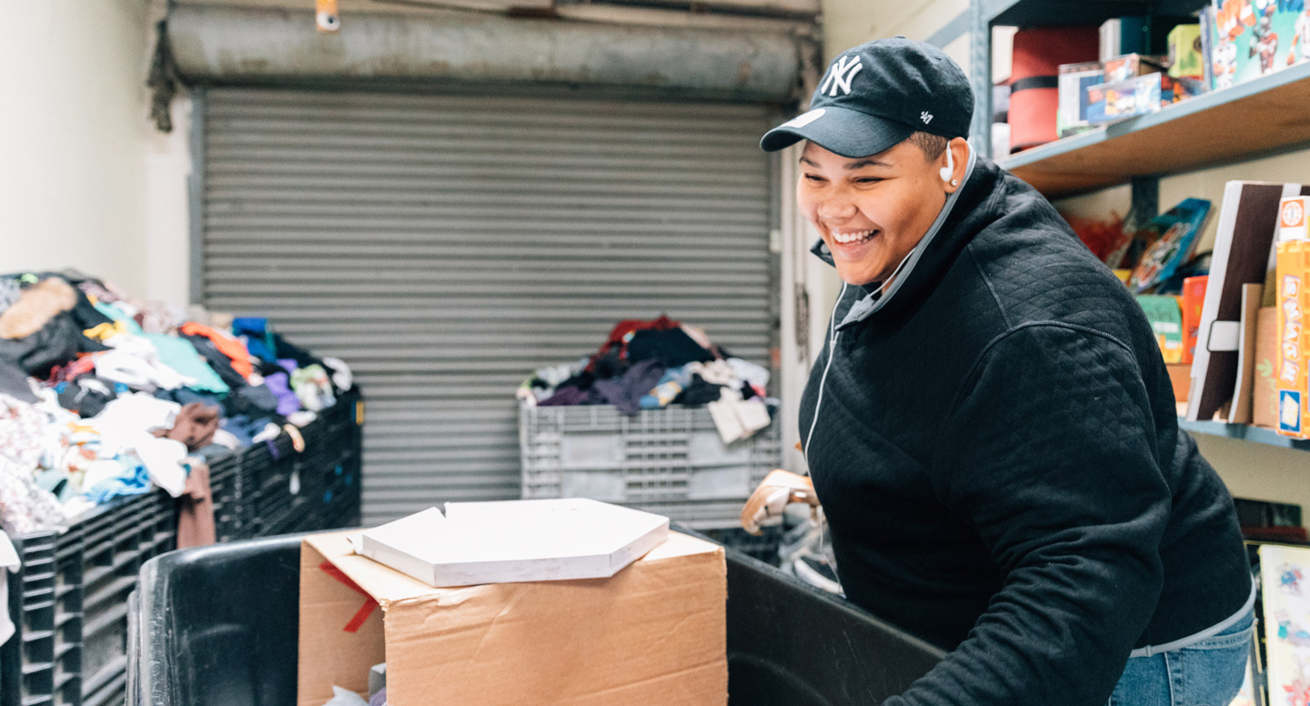 Smiling woman in black jacket and New York Yankees hat sorting donated goods and clothing at Ecumenical Hunger Program.