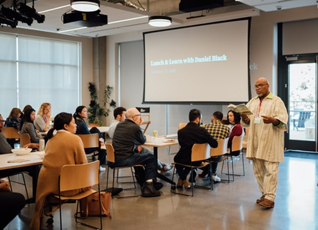 """The author reading aloud from his book to a group of attendees at """"Lunch & Learn with Daniel Black"""" (Diversity, Equity, & Inclusion)."""