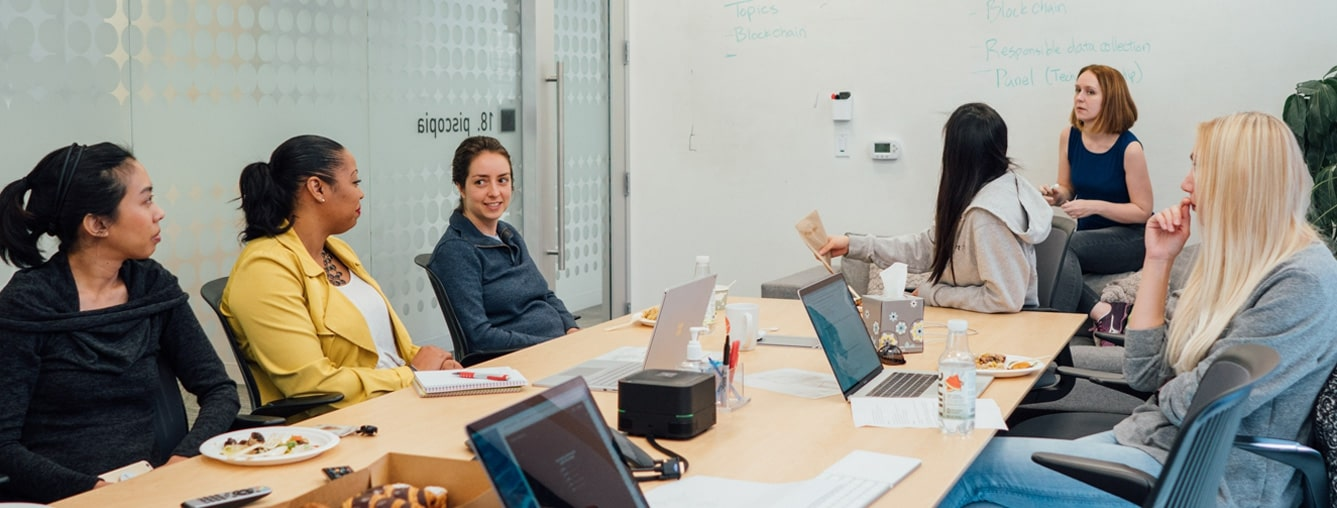 Group of CZI Women's Coding Circle members around a conference room table during a meeting (Diversity, Equity, & Inclusion).