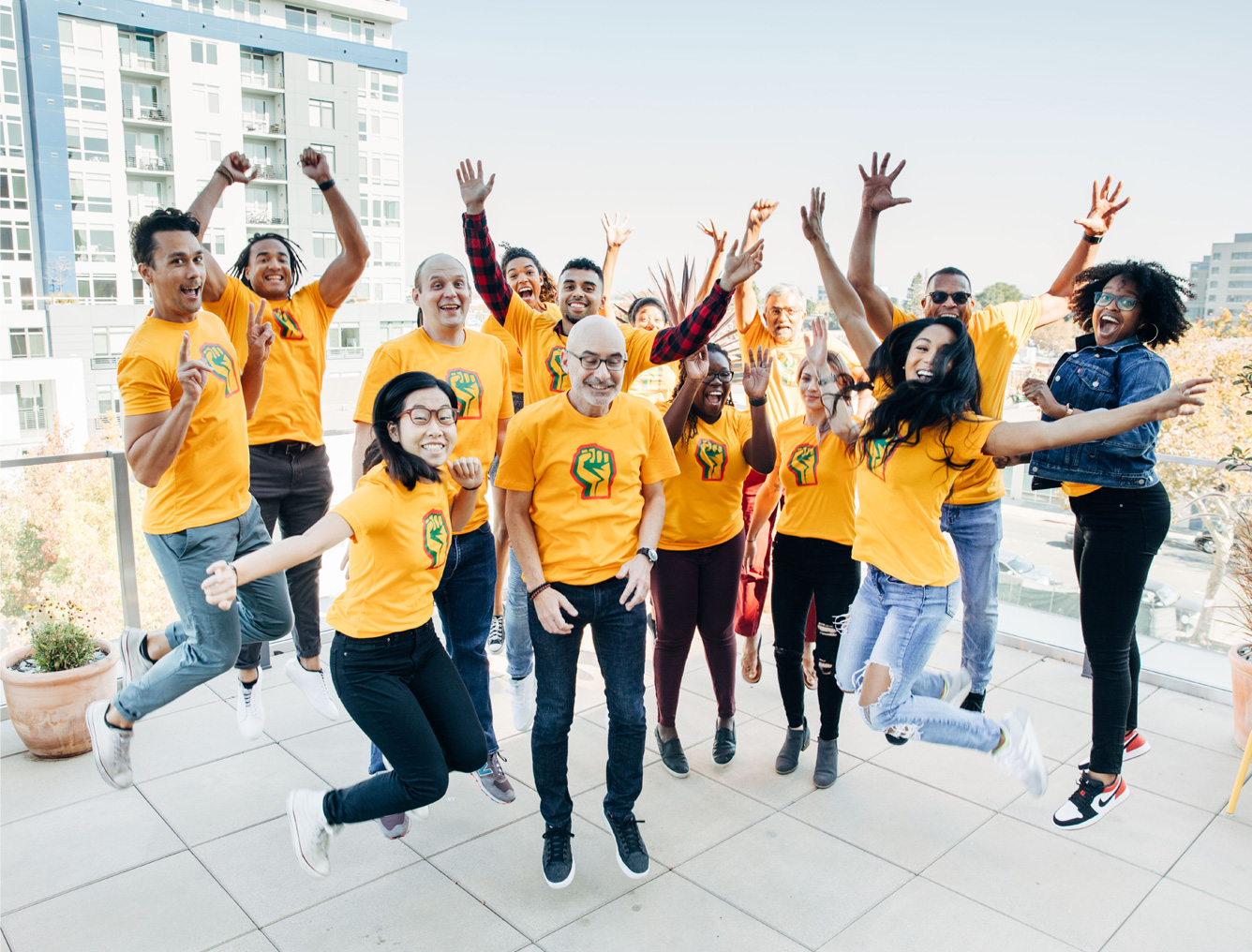 Group of CZI employees in symbolic power fist t-shirts, smiling and leaping in the air before heading out to AfroTech (Diversity, Equity, and Inclusion).