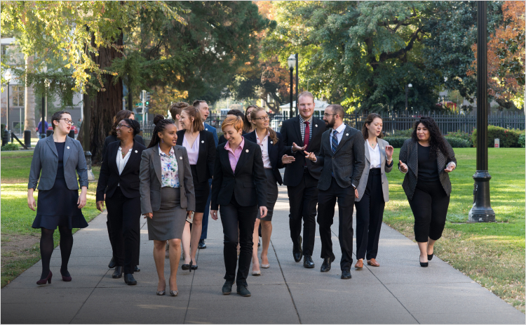 A group of more than 10 science and technology policy fellows dressed in formal clothing walk on a paved path through a grassy area.