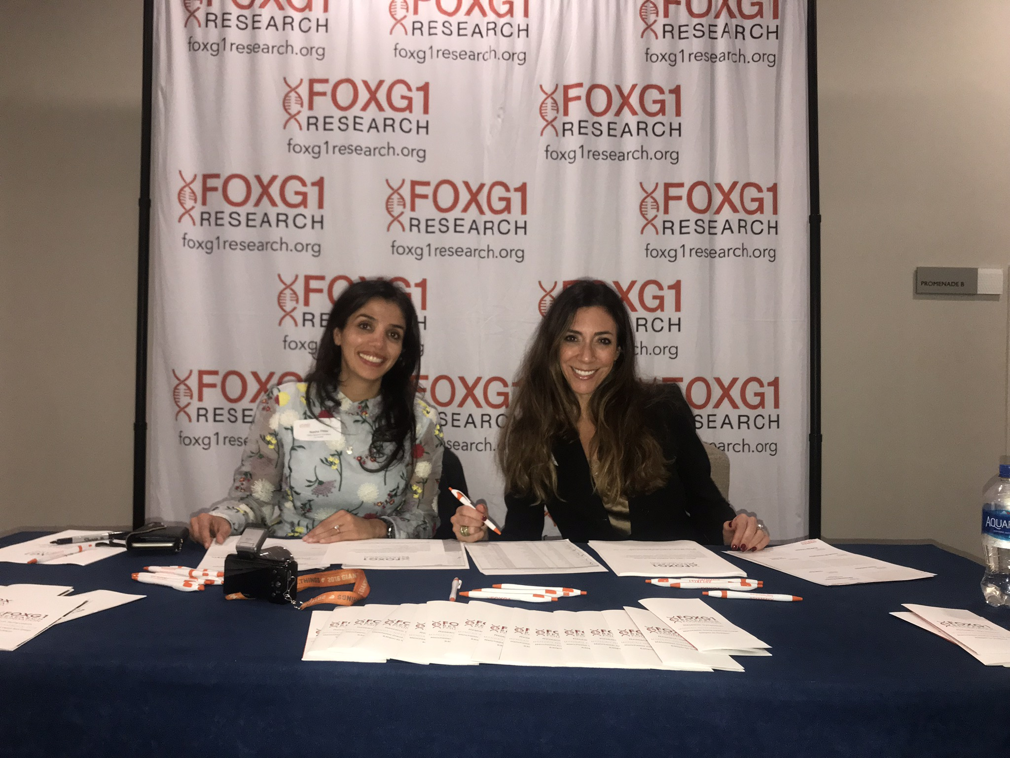FOXG1 Research Foundation co-founders Nasha Fitter and Nicole Johnson sit behind a table in a conference room smiling at the camera.