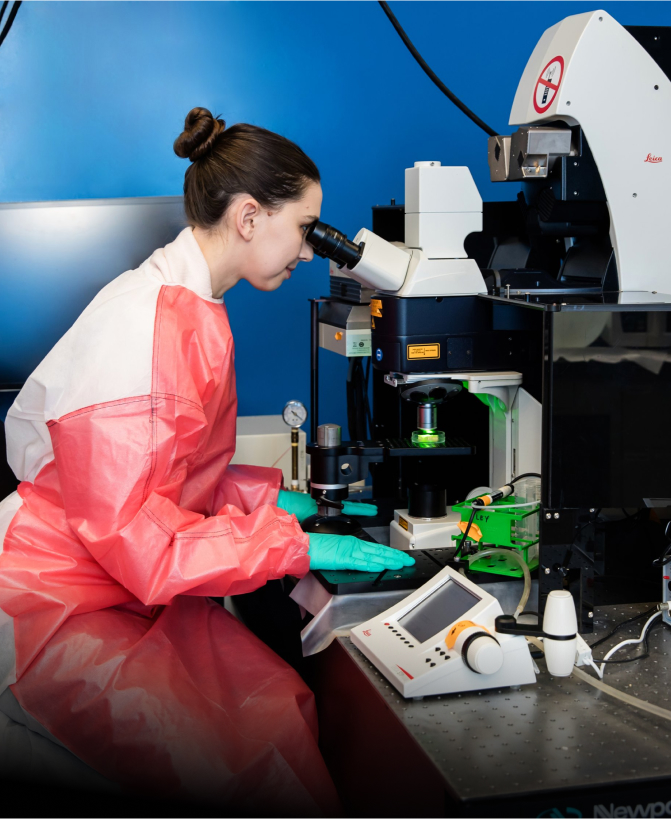 A scientist wearing a protective gown looks into a microscope