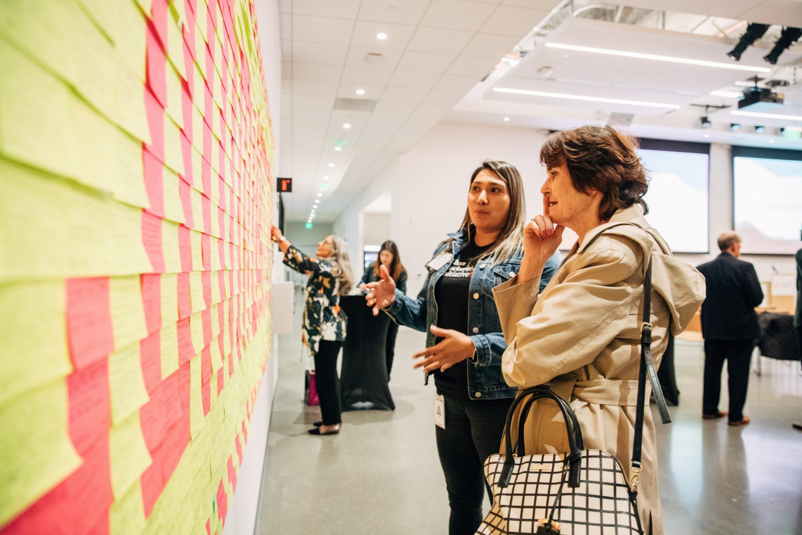 CZI Community team members and guests talking and studying wall of pink and yellow sticky notes, at the CZI Community Space opening in Redwood City.
