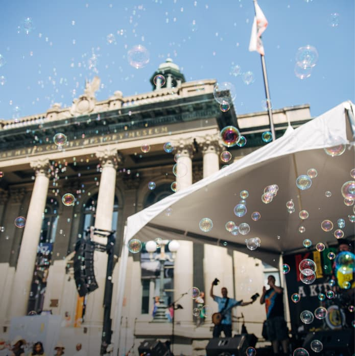 View of airborne bubbles and a live band in front of the courthouse in downtown Redwood City during Kidchella, an event sponsored by CZI (Community).