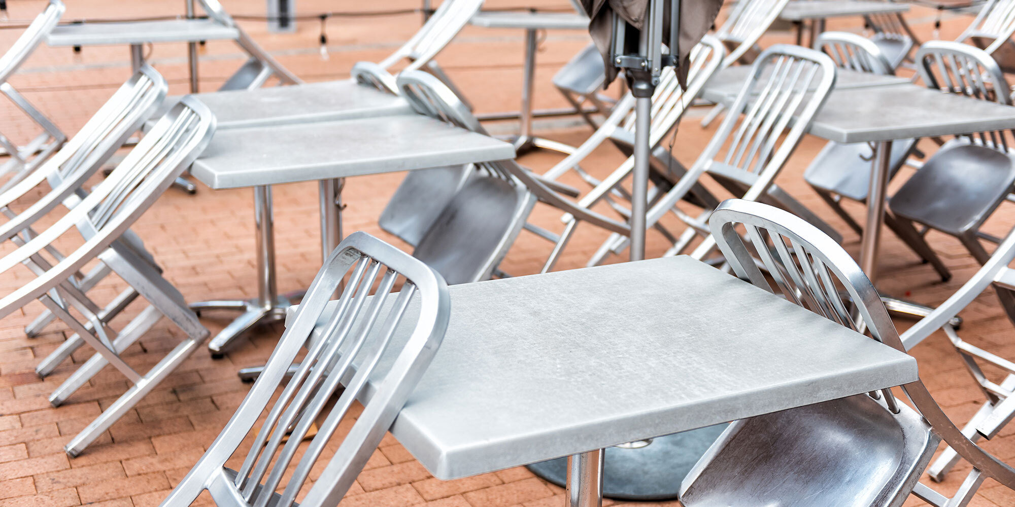 Many silver steel tables and chairs in closed cafe restaurant pattern outside outdoors, nobody, on street, closed umbrella