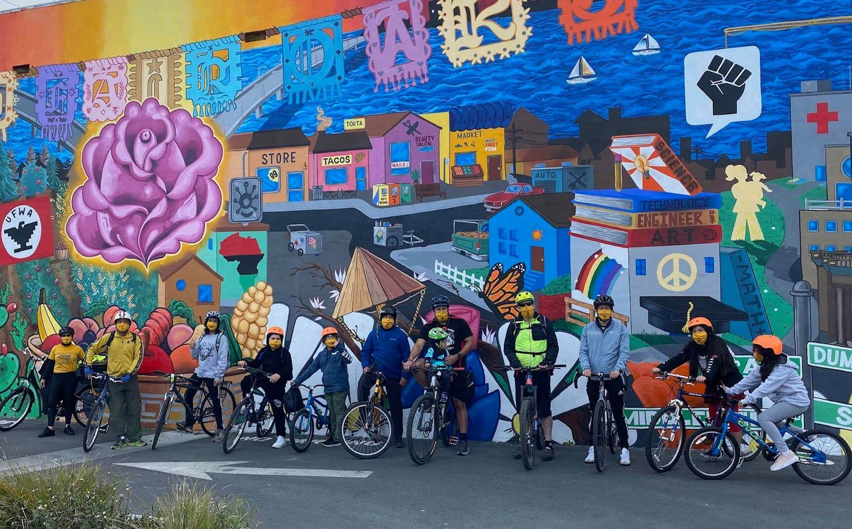 A group of community member sit on their bikes in front of a colorful mural.