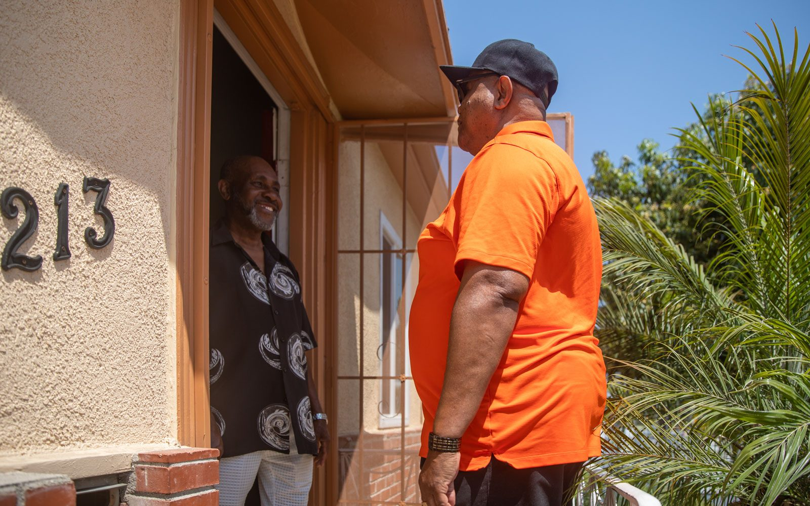 A man wears and orange shirt and black baseball cap and stand at the front door of a home where another man in a black shirt smiles.