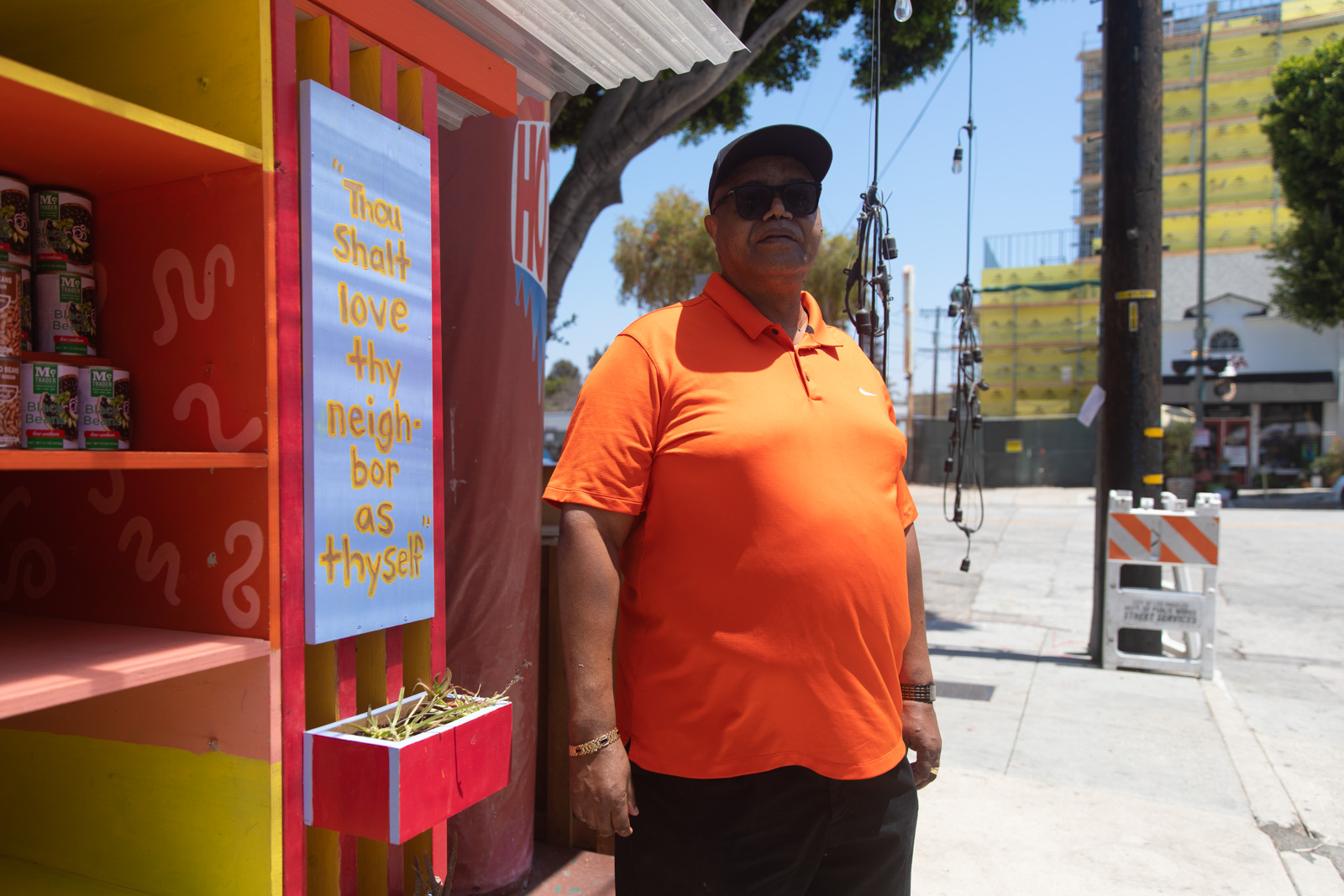 """A man in an orange shirt and black sunglasses stands outside next to a sign that reads """"Thou shalt live they neighbor as theyself."""""""