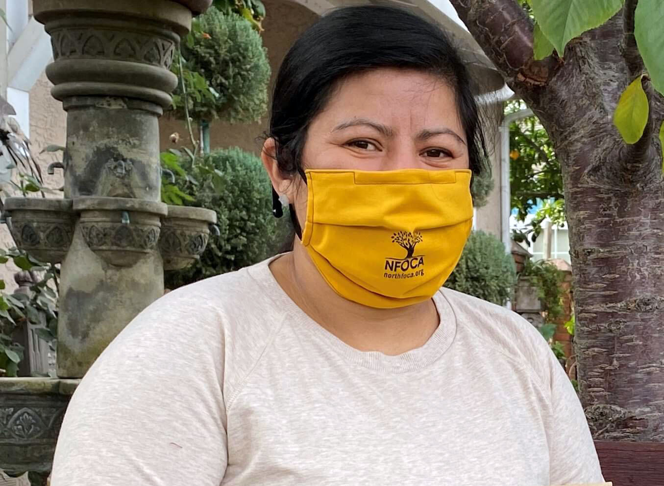 A woman in a tan shirt wears a yellow face mask and holds a brown bag with the NFOCA logo.