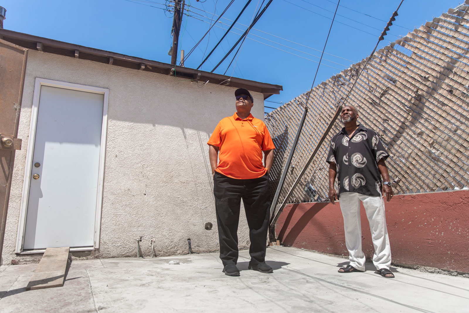 Two men look at the sky while standing in a backyard that's undecorated.