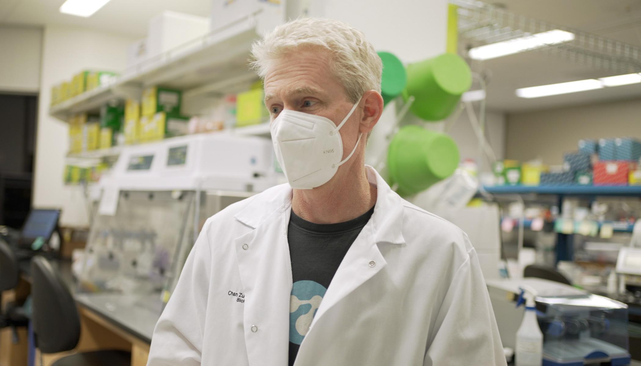 Joe DeRisi in white lab coat wears a N-95 mask in a COVID-19 lab.