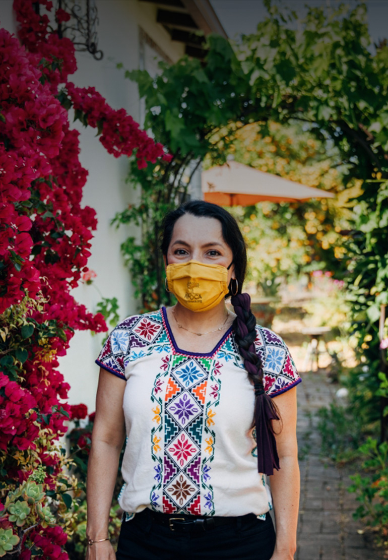 A woman in a colorful blouse, wears a yellow face mask bearing the NFOCA logo in her garden.