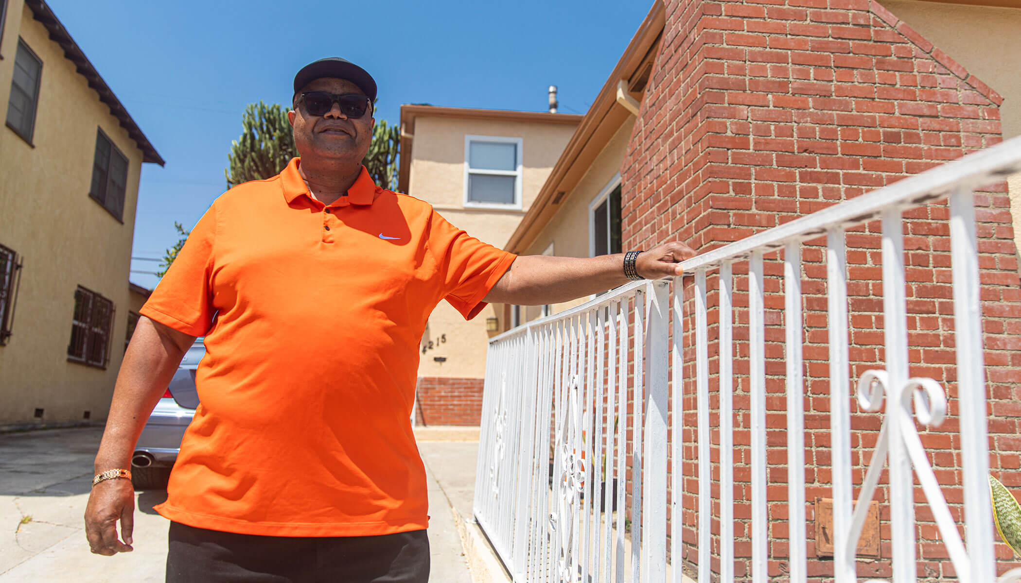 A man wears an orange shirt, sunglasses, and a baseball cap and rests his hand on a white fence.
