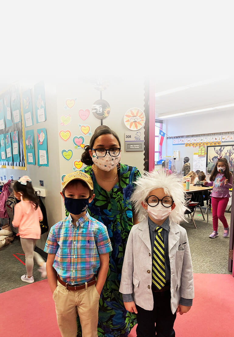 A student wears a messy white wig and lab coat, standing next to a classmate in a plaid top and baseball cap. Their teacher crouches behind them. All of them are wearing masks.