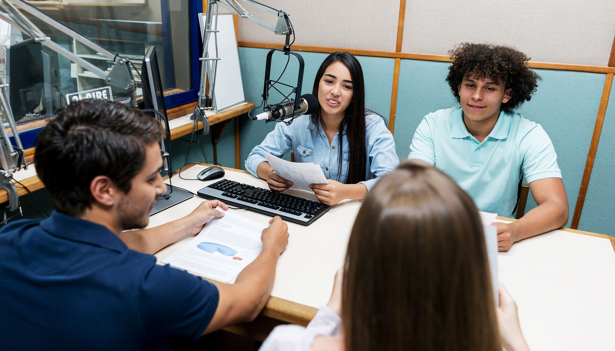 A group of four Latin American journalism students sit at a table in a radio studio with microphones.