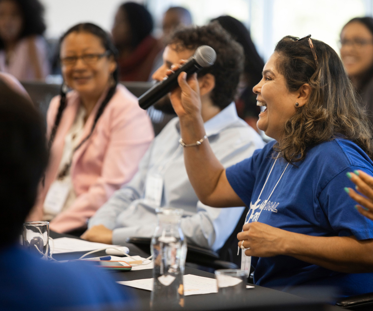National TPS Alliance members at a gathering, with woman in blue t-shirt holding a microphone and smiling in the foreground (CZI Movement & Capacity Building).