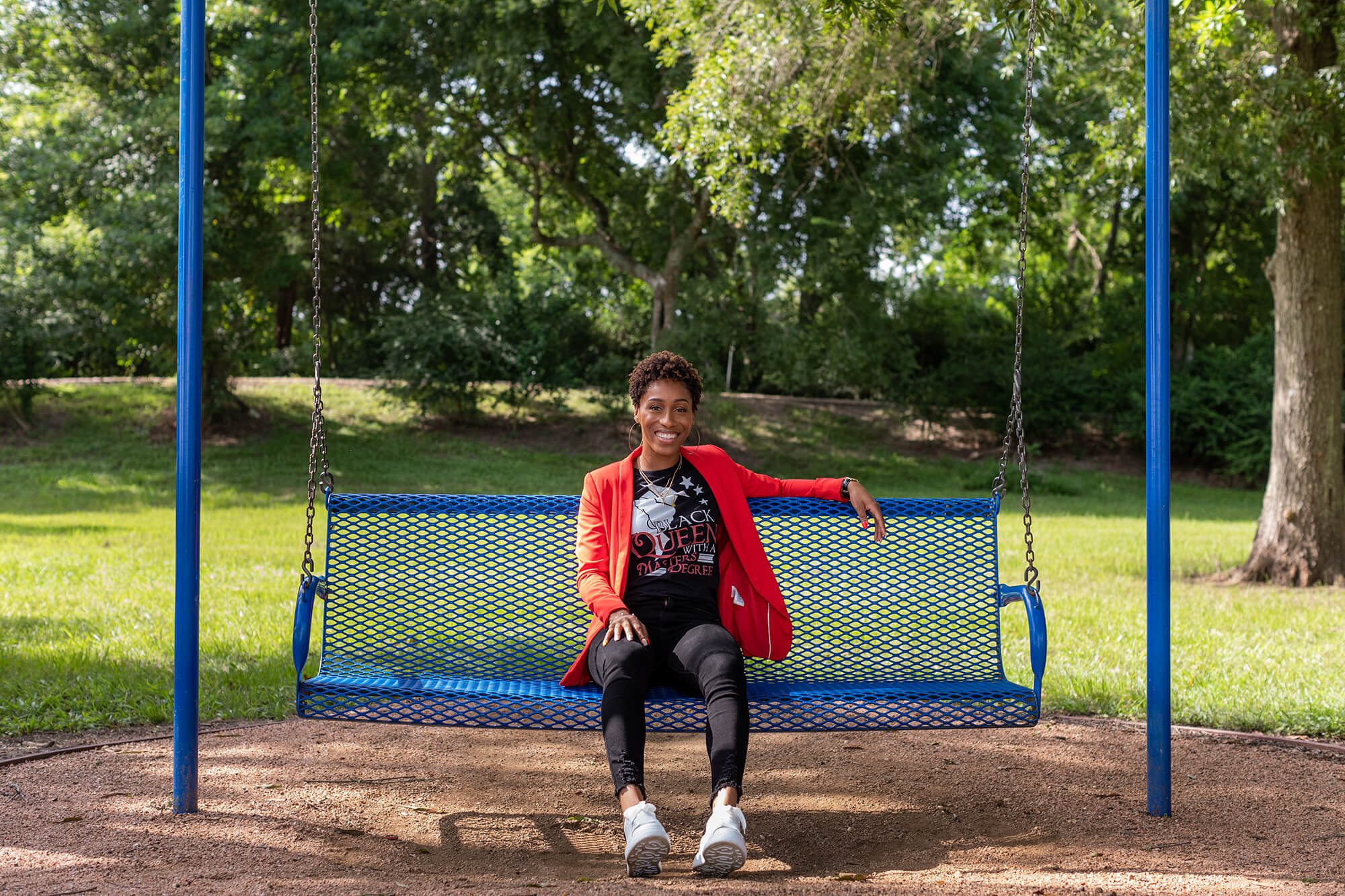 A woman in a red blazer sits on a blue bench in a park.