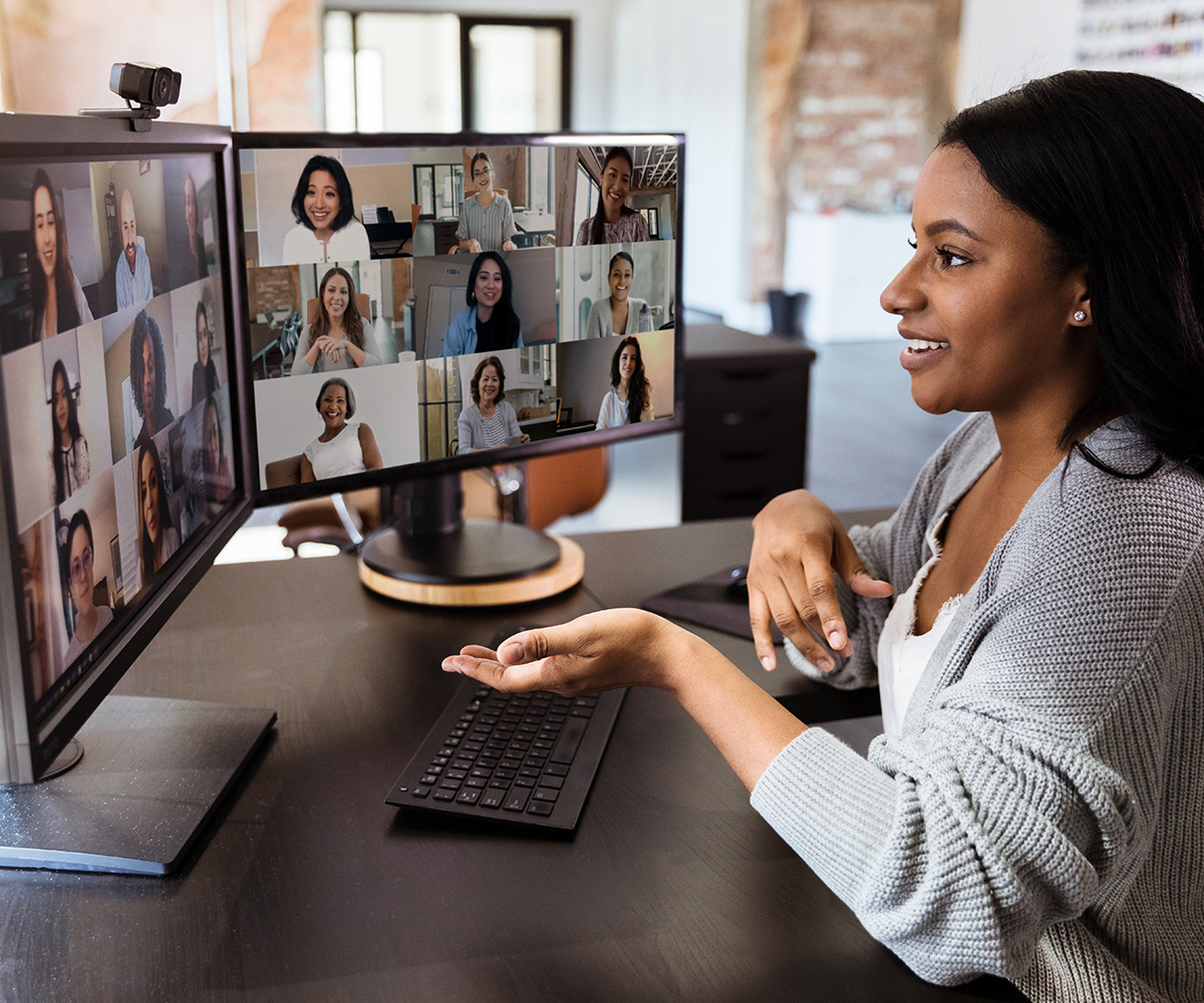 Photo of a woman seated in front of two computer monitors, participating in an online CZI capacity building training session with multiple attendees.