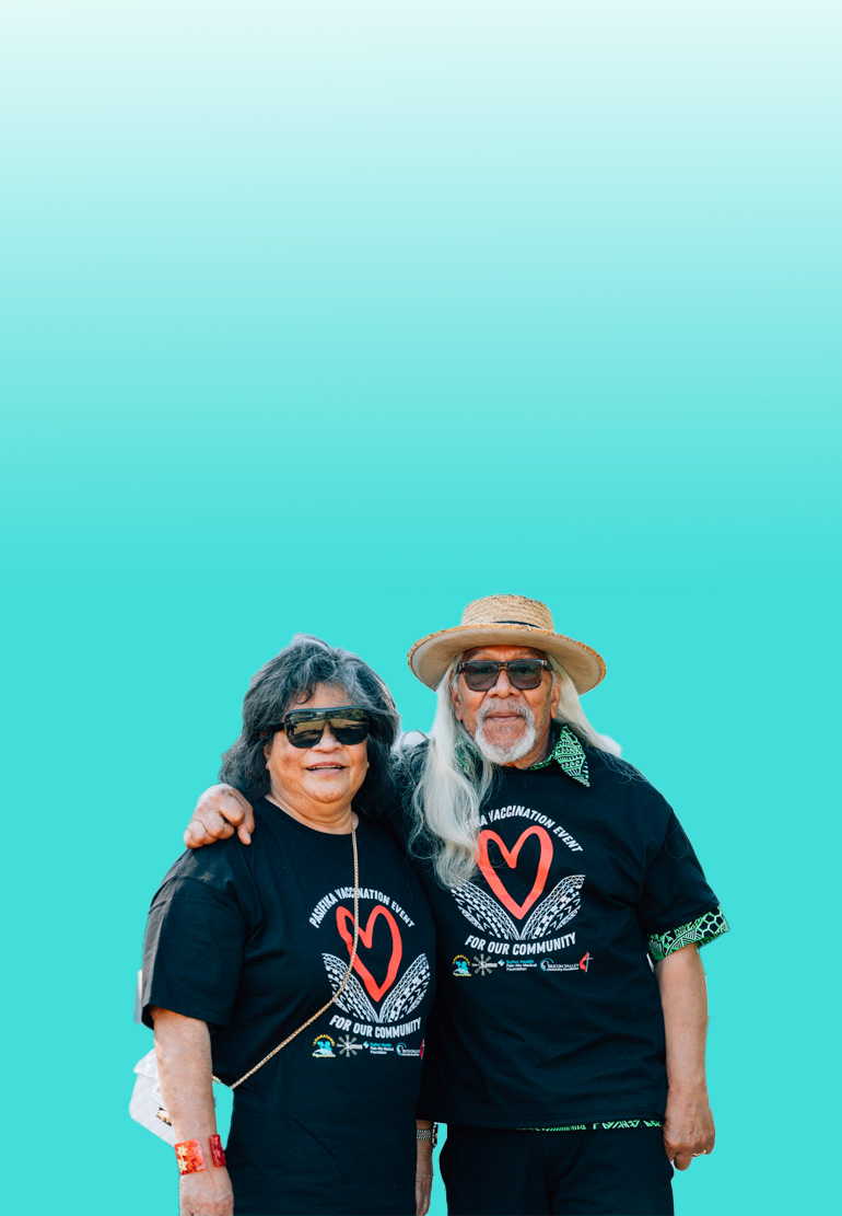 A man and a women pose together. Both are wearing black shirts with red hearts printed on them.