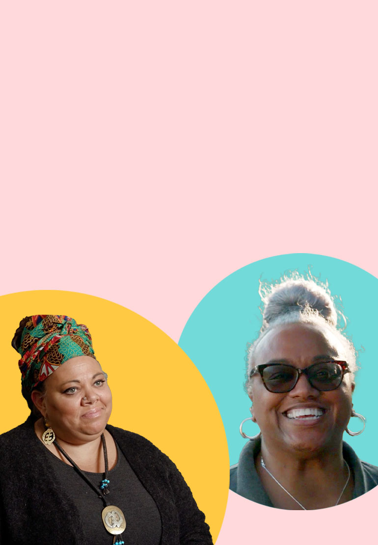 A woman with a colorful head wrap smiles and is pictured next to another woman with glasses who also smiles.